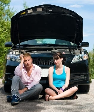 A couple is stranded on the road in front of their car