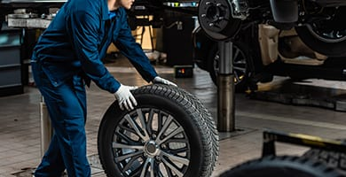 young mechanic holding car wheel near raised car in workshop
