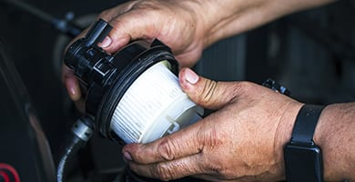 Car mechanic replace the new fuel filter at modern diesel engine. car service or preventive maintenance.